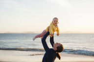 Mother lifting up little daughter on the beach - DIGF03240