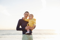 Mother holding little daughter on the beach - DIGF03243