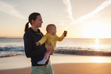Mother holding little daughter on the beach at sunset - DIGF03246