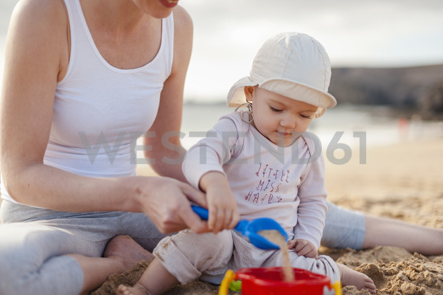 Mother playing with little daughter on the beach - DIGF03249