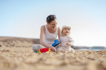 Mother playing with little daughter on the beach - DIGF03252