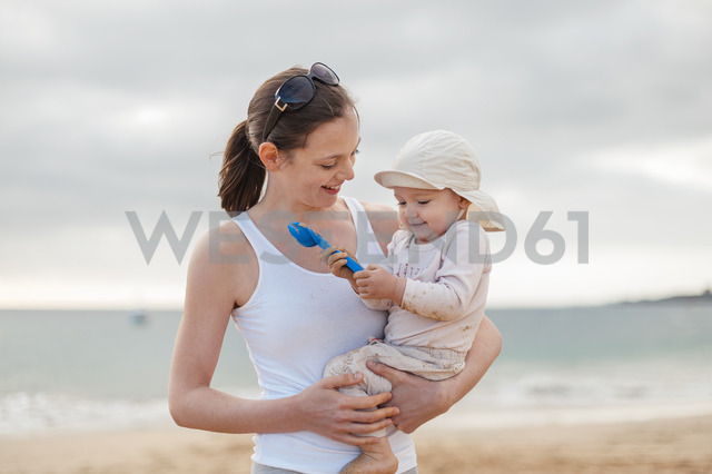 Mother holding little daughter on the beach - DIGF03258