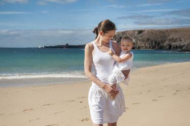 Mother holding little daughter on the beach - DIGF03261