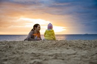 Mother with little daughter on the beach at sunset - DIGF03267