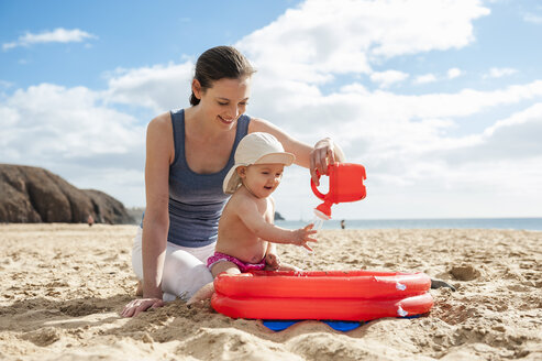 Mother playing with little daughter on the beach - DIGF03270