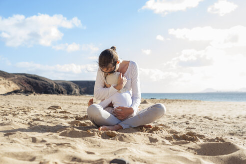Mother cuddling with little daughter on the beach - DIGF03273