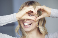 Portrait of laughing woman building heart with her fingers - PNEF00524