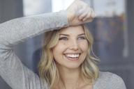 Portrait of happy woman looking out of window - PNEF00527