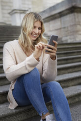 Portrait of happy young woman sitting on stairs using smartphone - PNEF00530