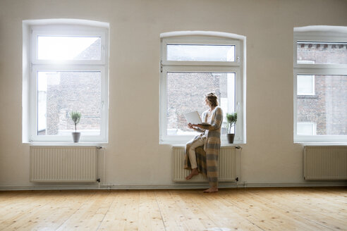 Mature woman in empty room holding laptop at the window - MOEF00734
