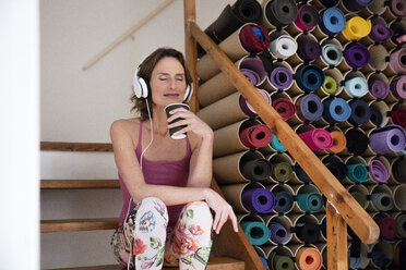 Relaxed mature woman listening to music next to assortment of yoga mats - MOEF00737