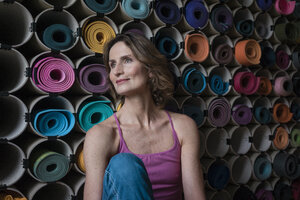 Smiling mature woman in front of assortment of yoga mats - MOEF00743