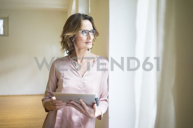 Mature woman in empty room holding tablet at the window - MOEF00749