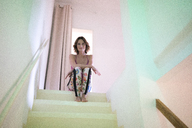 Portrait of smiling mature woman sitting in staircase - MOEF00752
