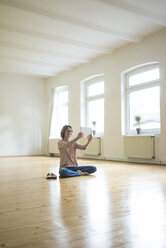 Smiling mature woman sitting on floor in empty room taking selfie with tablet - MOEF00755