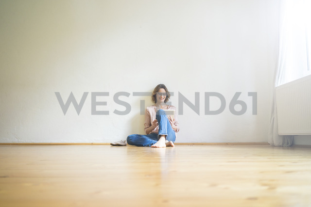 Smiling mature woman sitting on floor in empty room using tablet - MOEF00758