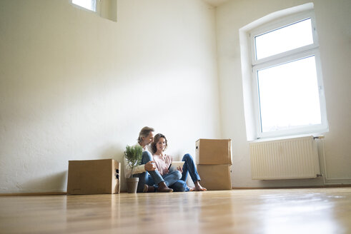Mature couple sitting on floor in empty room next to cardboard boxes using tablet - MOEF00761