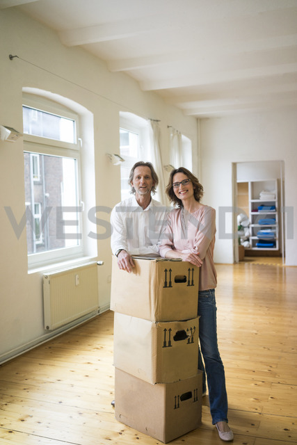 Smiling mature couple standing in empty room with cardboard boxes - MOEF00764