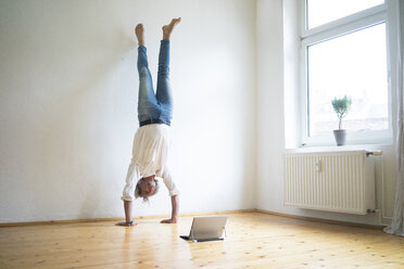 Mature man doing a handstand on floor in empty room looking at tablet - MOEF00767