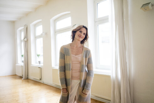 Portrait of smiling mature woman standing in empty room - MOEF00776