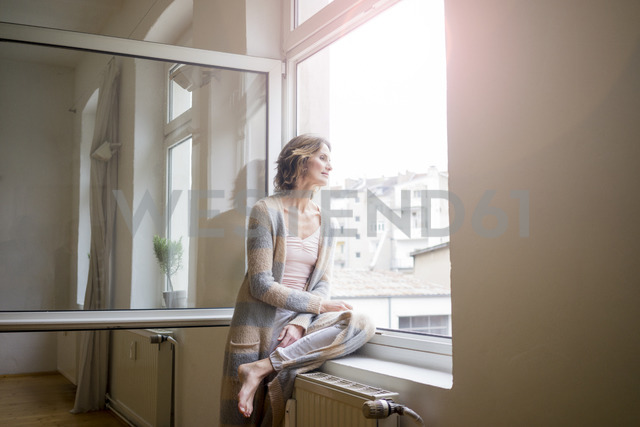 Mature woman looking out of window - MOEF00779