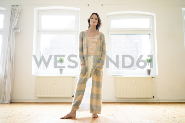 Portrait of smiling mature woman standing in empty room - MOEF00782