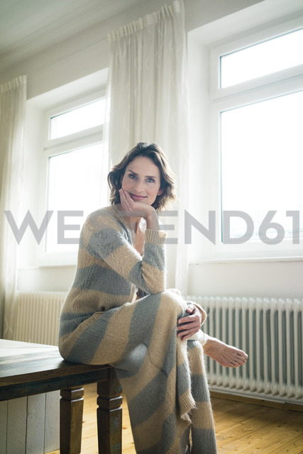 Portrait of smiling mature woman sitting on wooden bench at home - MOEF00788