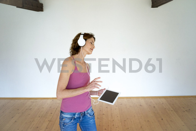 Mature woman listening to music in empty room - MOEF00794