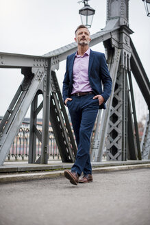 Stylish mature businessman wearing blue suit walking on bridge - DIGF03278