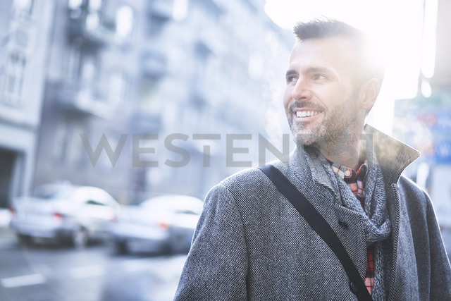 Portrait of laughing man on city street in winter - BSZF00230
