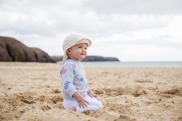Spain, Lanzarote, content baby girl crouching on the beach - DIGF03286
