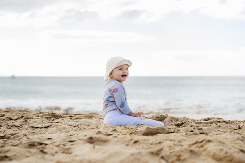 Spain, Lanzarote, laughing baby girl sitting on the beach - DIGF03289