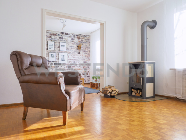 Germany, modern living room, leather chair and fireplace - LAF01962