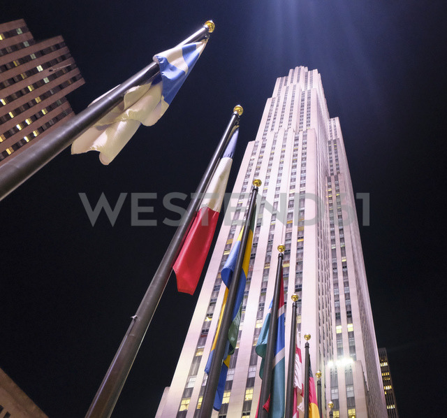 USA, New York City, international flags in front of Rockefeller Center at night - SEEF00017