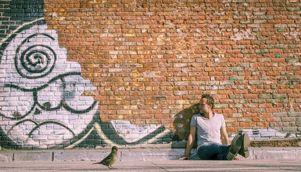 USA, New York City, man sitting at brick wall with graffiti and sparrow in foreground - SEE00032