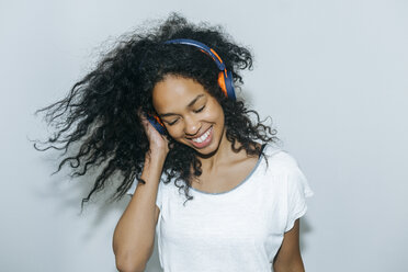 Portrait of happy young woman listening music with headphones - KIJF01902