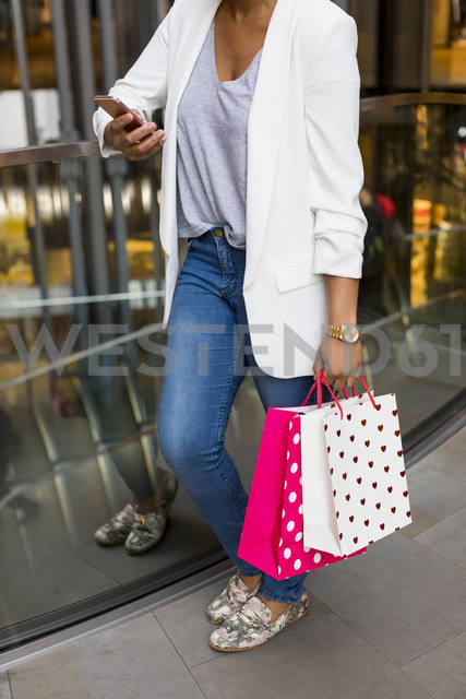 Woman using cell phone in shopping mall - MAUF01338