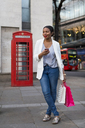UK, London, smiling woman with cell phone holding shopping bags in the city - MAUF01341