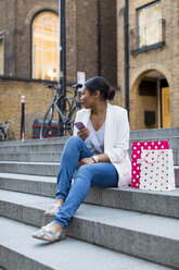 UK, London, woman with shopping bags and cell phone sitting on stairs in the city - MAUF01344