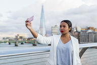 UK, London, woman standing on a bridge taking a selfie - MAUF01347