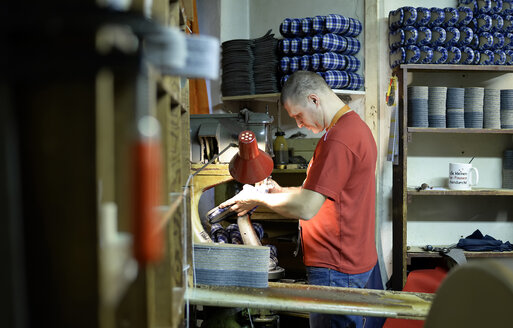 Shoemaker working on slippers in workshop - BFRF01816