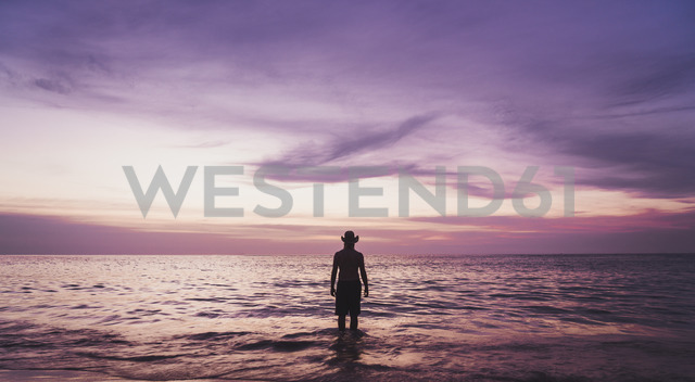 Thailand, Phuket, silhouette of man wearing hat wading at seafront by sunset - KKAF00865