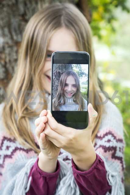 Portrait of laughing girl taking selfie with cell phone - SARF03551