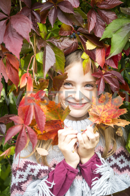 Portrait of happy girl hiding behind autumn leaves - SARF03554