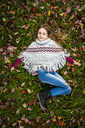 Portrait of smiling girl wearing poncho lying on autumnal meadow - SARF03557