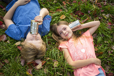 Boy and girl on a meadow having fun with tin can phone - SARF03560