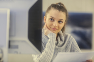 Portrait of young woman working at desk in an office - SGF02172