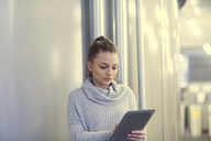 Portrait of serious young woman using tablet in an office - SGF02175