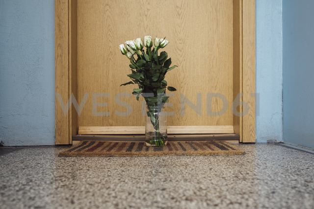 Vase with farewell flowers on floor mat at apartment door of deceased neighbour - JSCF00058 - Jonathan Schöps/Westend61