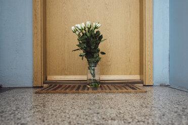 Vase with farewell flowers on floor mat at apartment door of deceased neighbour - JSCF00058